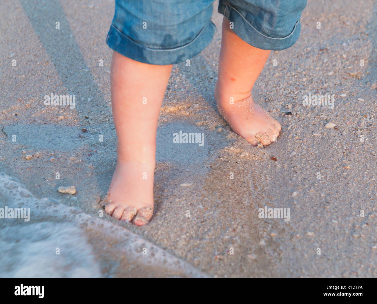 Bare feet walking at sandy beach near the sea. Little baby in blue jeans shorts going to touch the sea at sunset. Wave washes baby's feet. Toned. Soft focus. - Stock Image