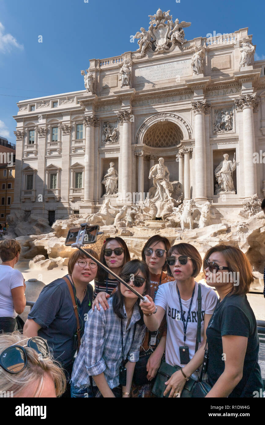 Tourists taking a group selfie photograph in front of the Trevi Fountain,  Rome, Italy. Stock Photo