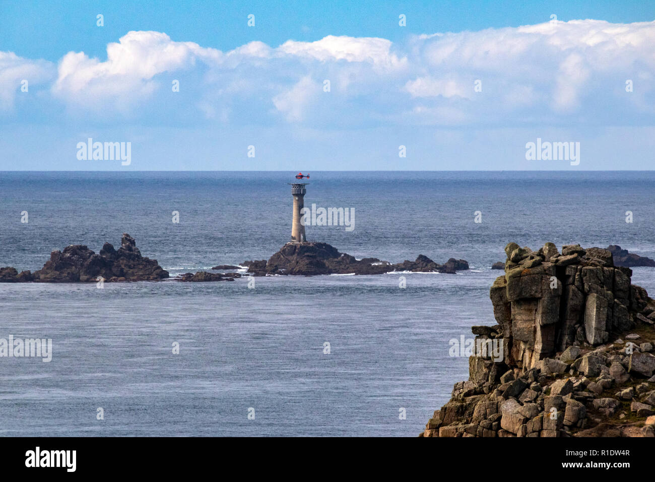 Longship Lighthouse with approaching Helicopter; Carn Bras, Longship Rocks Lighthouse, near Lands End, Cornwall, England. - Stock Image