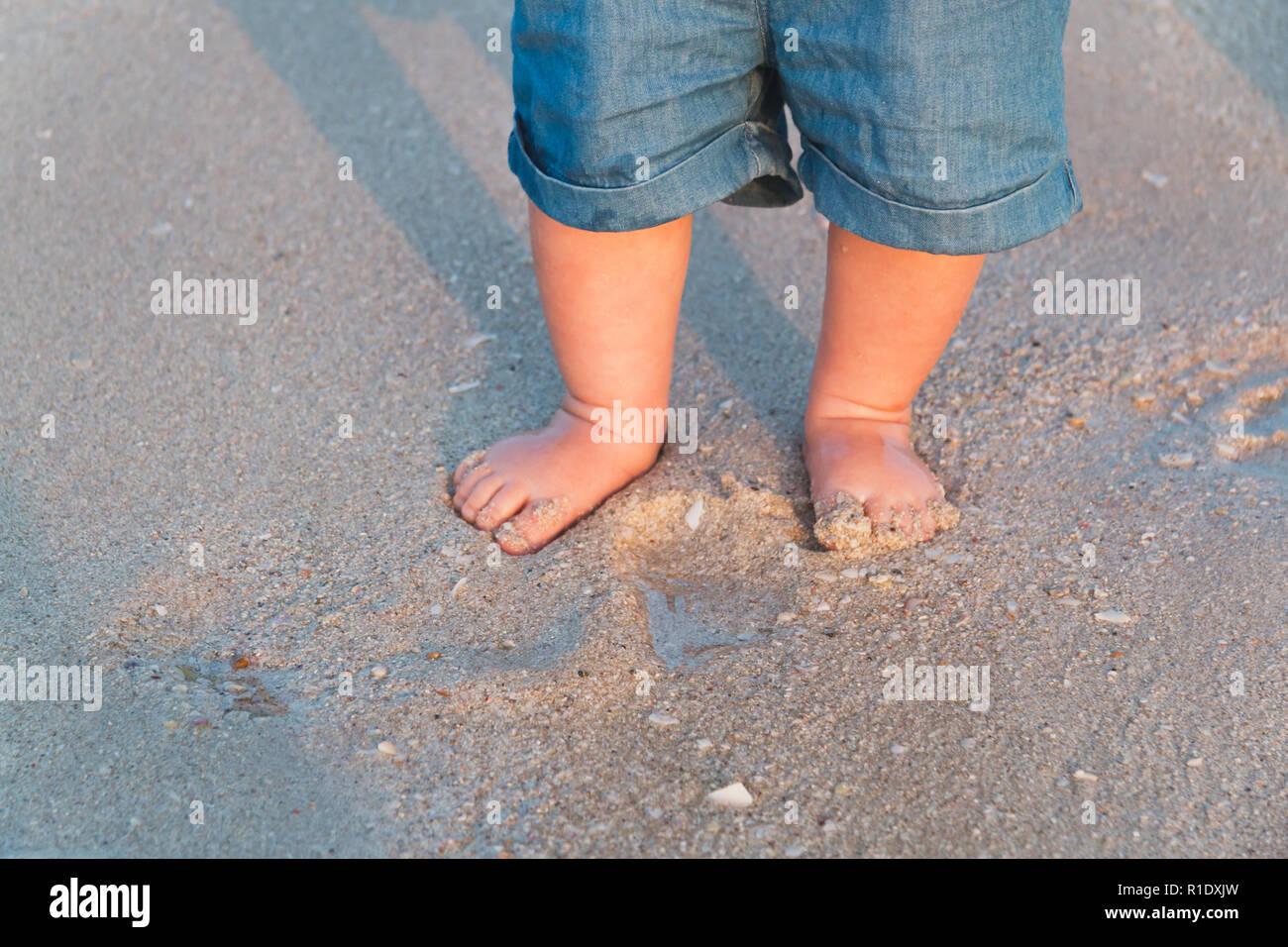64793e4dbc03 Bare feet walking at sandy beach near the sea. Little baby in blue jeans  shorts