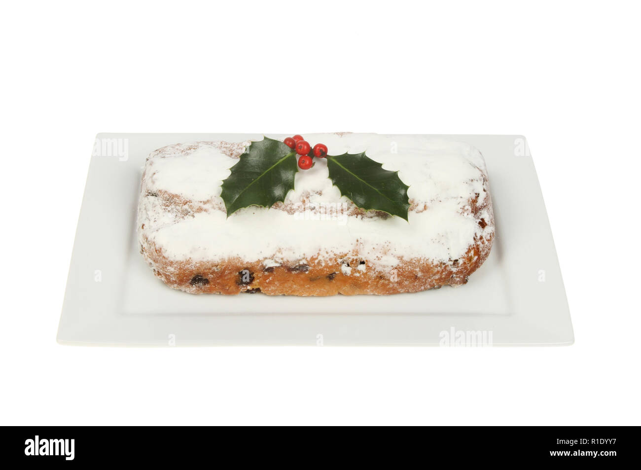 Marzipan stollen on a plate decorated with holly isolated against white - Stock Image