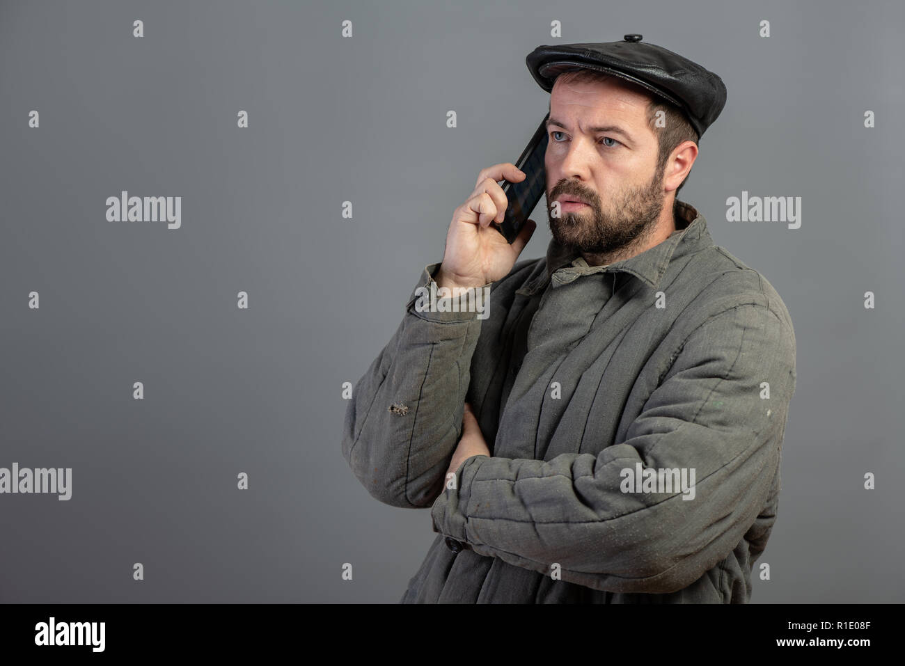 Serious caucasian man 35 years old speaks on mobile phone, studio shot. Idea - village dweller and modern technology, set Stock Photo