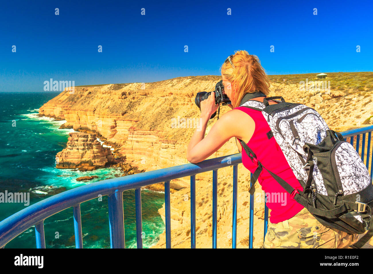 Travel photographer takes shot of Natural Bridge lookout in Kalbarri National Park, Western Australia, Australian Outback. Female tourist takes pictures with professional camera of Indian Ocean cliffs - Stock Image