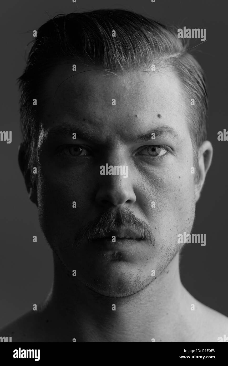 Face of young Caucasian man with mustache shirtless - Stock Image