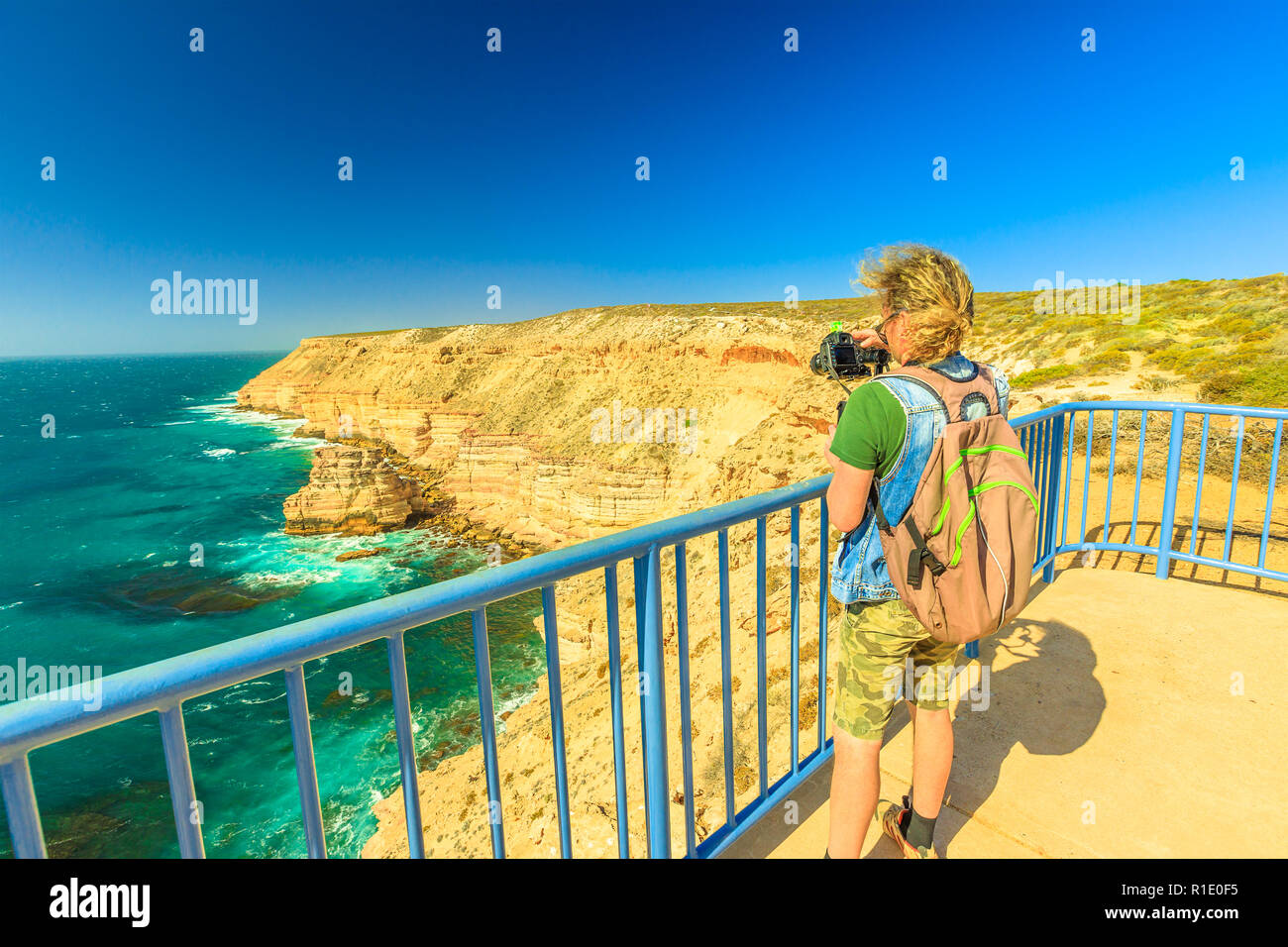 Travel photographer with stabilizer takes shot of Natural Bridge lookout in Kalbarri National Park, WA, Australian Outback. Videomaker with professional camera takes photo of Indian Ocean cliffs. - Stock Image