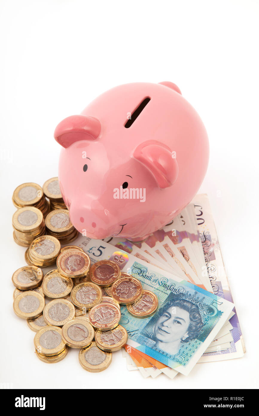 Pink Piggy bank on lots of pound notes and pound coins Stock Photo
