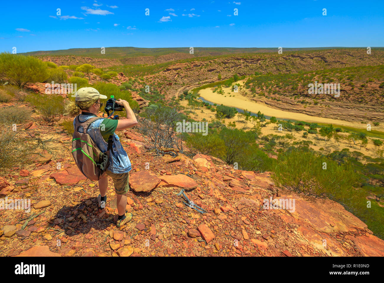 Travel photographer backpacker with stabilizer takes shot at Murchison River Gorge in Kalbarri National Park, Western Australia. Videomaker with professional camera takes photo in Australian outback. - Stock Image