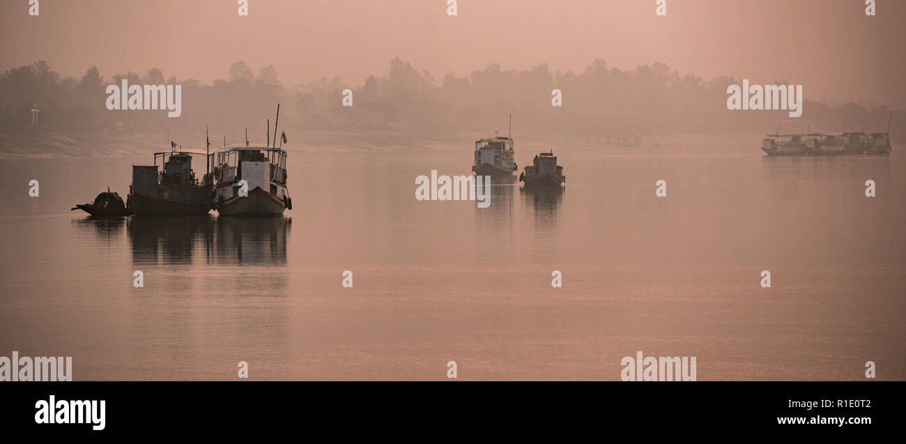 Anchored fishing boats on a foggy morning in the Subarbans, West Bengal, India Stock Photo