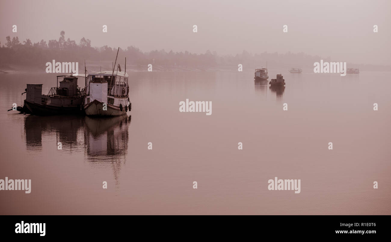Anchored fishing boats on a foggy morning in the Subarbans, West Bengal, India - Stock Image