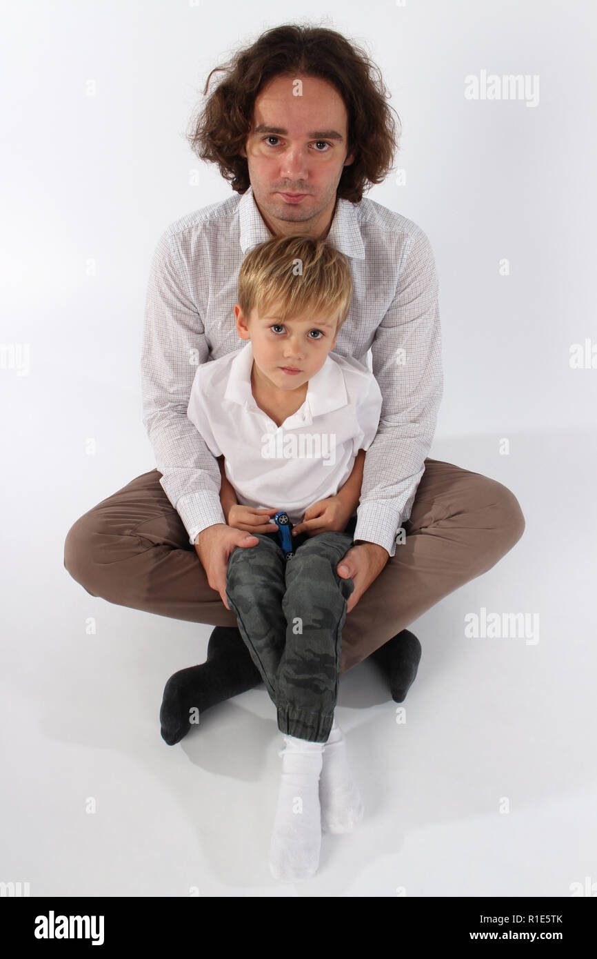 Adorable child boy in his daddy's lap - Stock Image