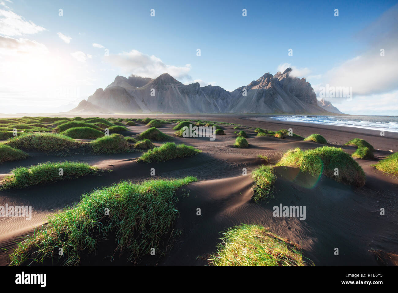 Fantastic west of the mountains and volcanic lava sand dunes on the beach Stokksness, Iceland. Colorful summer morning Iceland, Europe - Stock Image