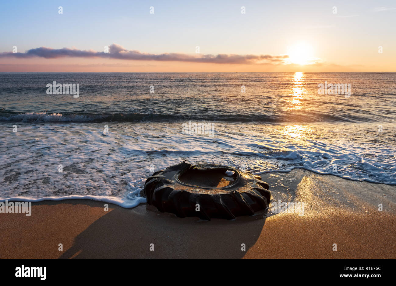 Tyre on the beach. Beautiful sunrise and dirty beach. Stock Photo