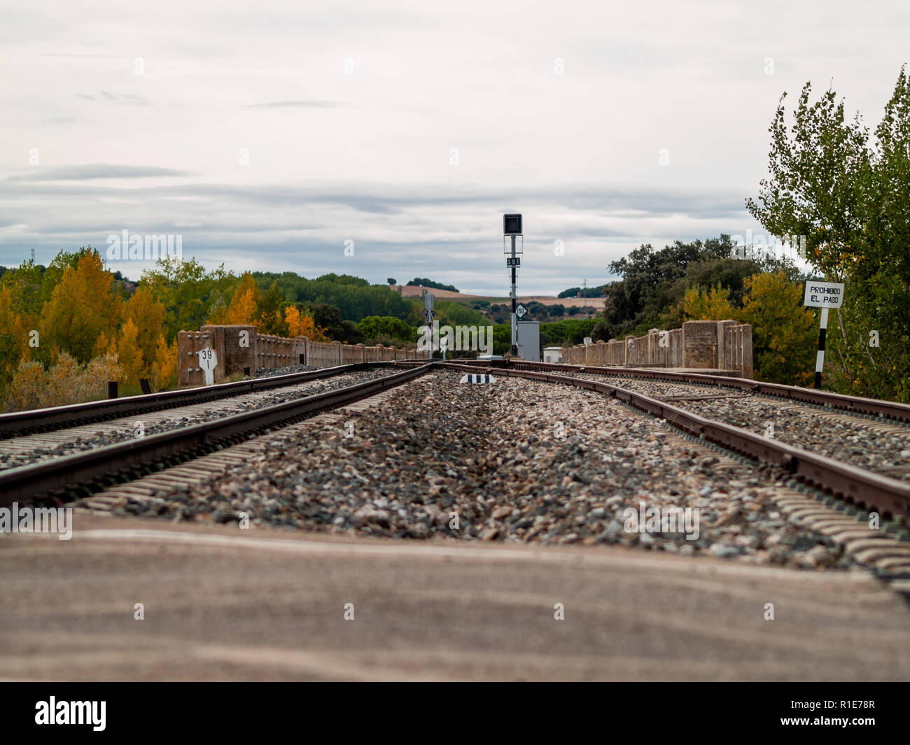 Crossroads on train tracks that go through a landscape in autumn with clouds in the sky Stock Photo