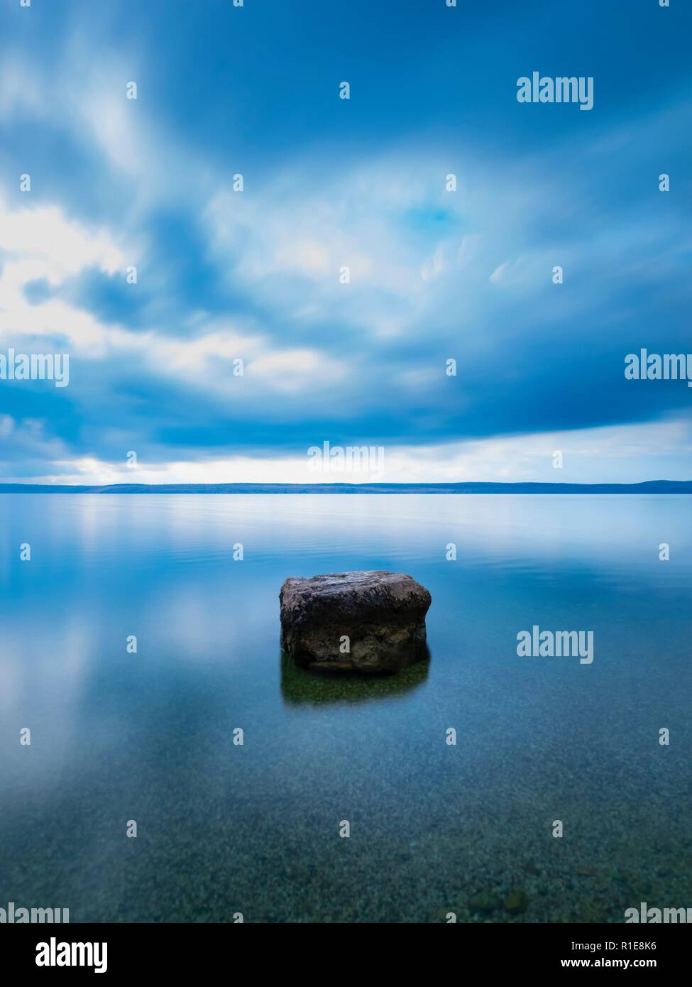 Long exposure lonely rock on smooth glass-like sea surface - Stock Image