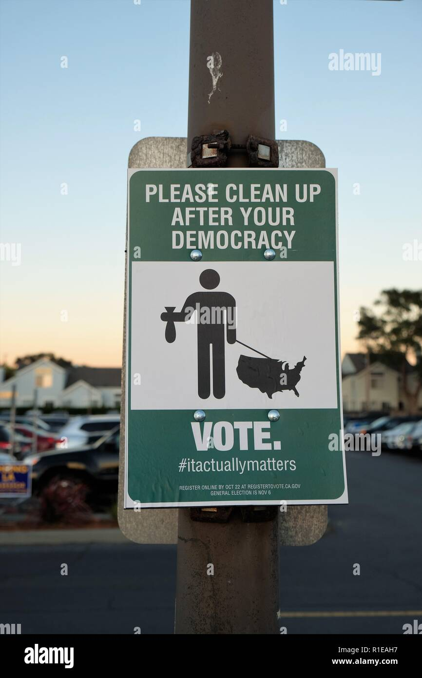 Sign on a light post: 'Please clean up after your democracy Vote'; voter drive, encouragement; urgency for people to vote; Oakland, California, USA. - Stock Image
