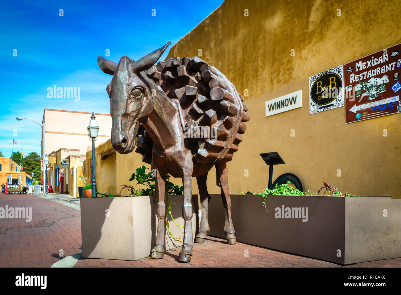 The bronze burro statue loaded down with firewood greets visitors at the entrance to Burro Alley with it's infamous history in downtown Santa Fe, NM - Stock Image