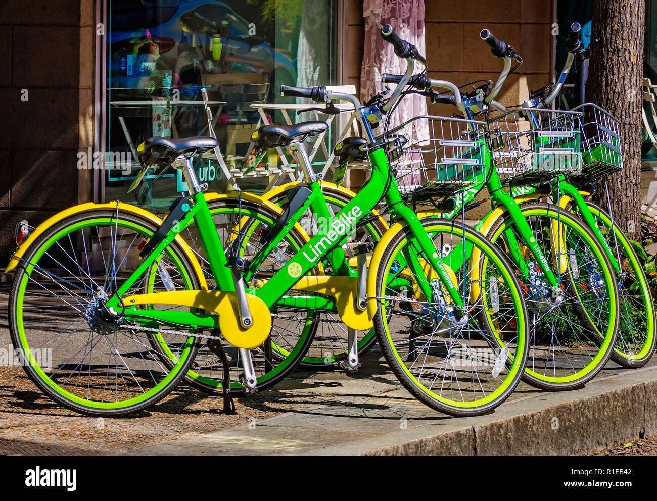 A row of LimeBikes, a bike-sharing service, is parked against a shop on Dauphin Street, Nov. 3, 2018, in Mobile, Alabama. Stock Photo