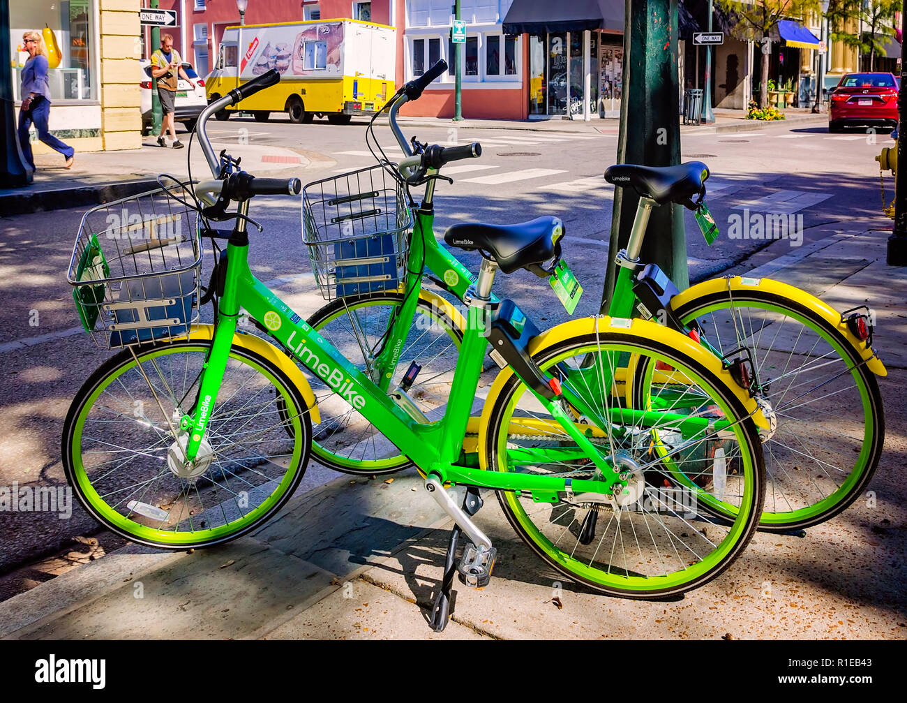 A LimeBike, part of a bike-sharing service, is parked against a tree on Dauphin Street, Nov. 3, 2018, in Mobile, Alabama. Stock Photo