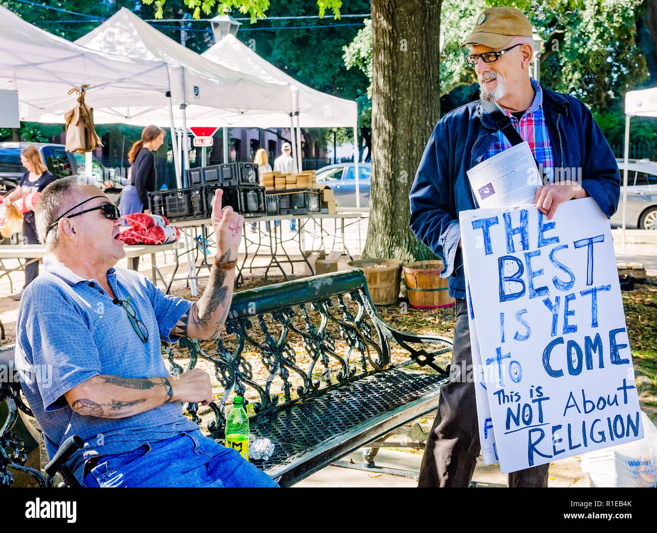 Two men discuss politics and current events at Market in the Park in Cathedral Square, Nov. 3, 2018, in Mobile, Alabama. - Stock Image