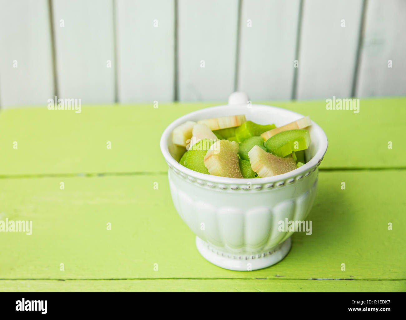 Fresh ripe rhubarb (Rheum rhabarbarum) peeled and cut into pieces in a white vintage cup. Prepared for cooking. Green and white wooden background. - Stock Image