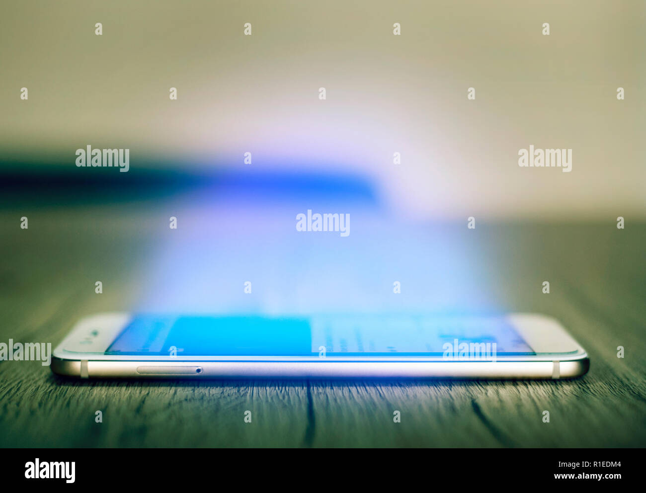 Side view of Smartphone on the wooden table with inviting blue light glowing coming from the screen. Addicted to internet concept. Selective focus on - Stock Image