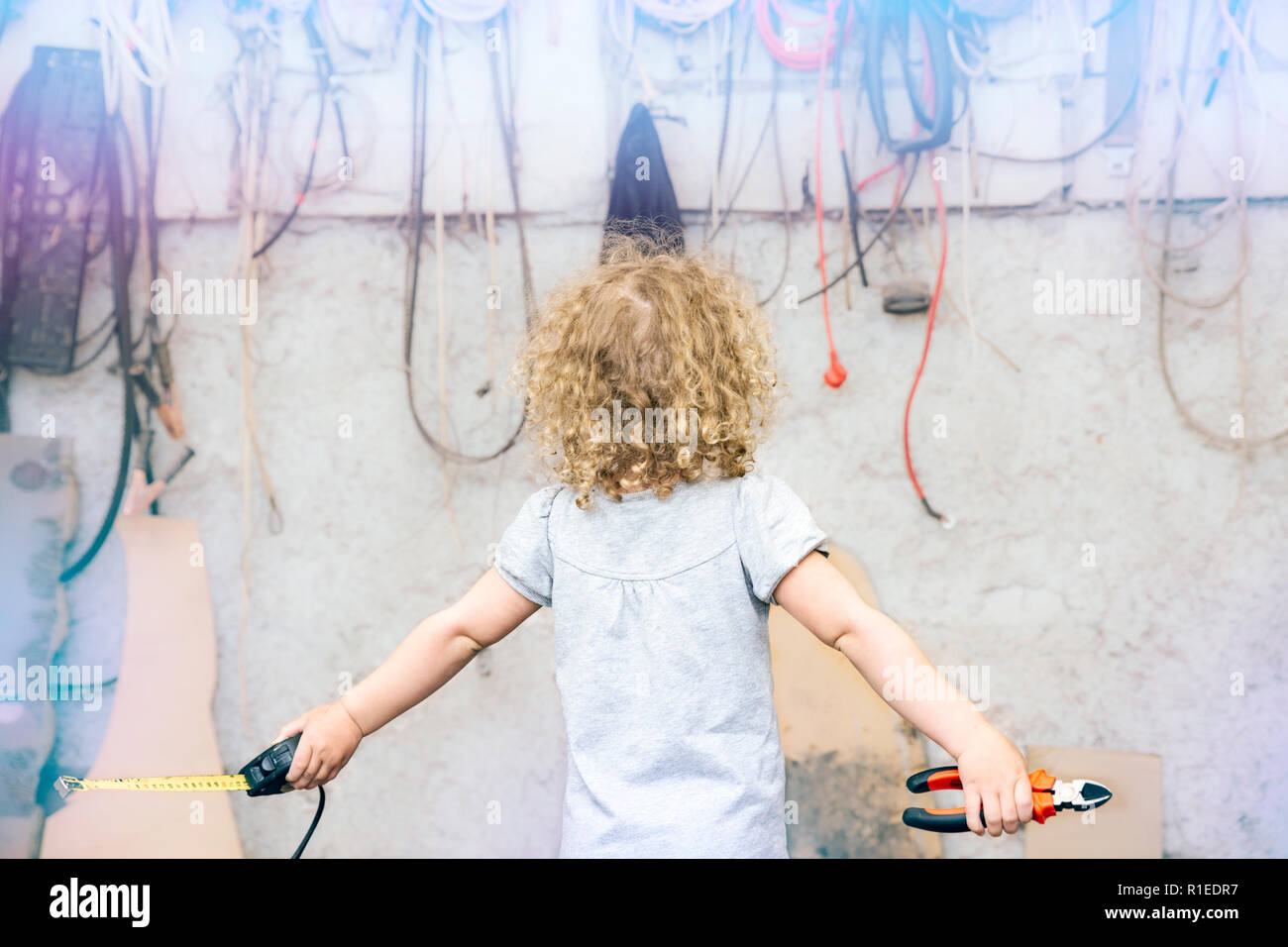 Young girl child hand holding pliers and measuring tape facing the problems, organizes mess on the background, conquering problems concept. - Stock Image
