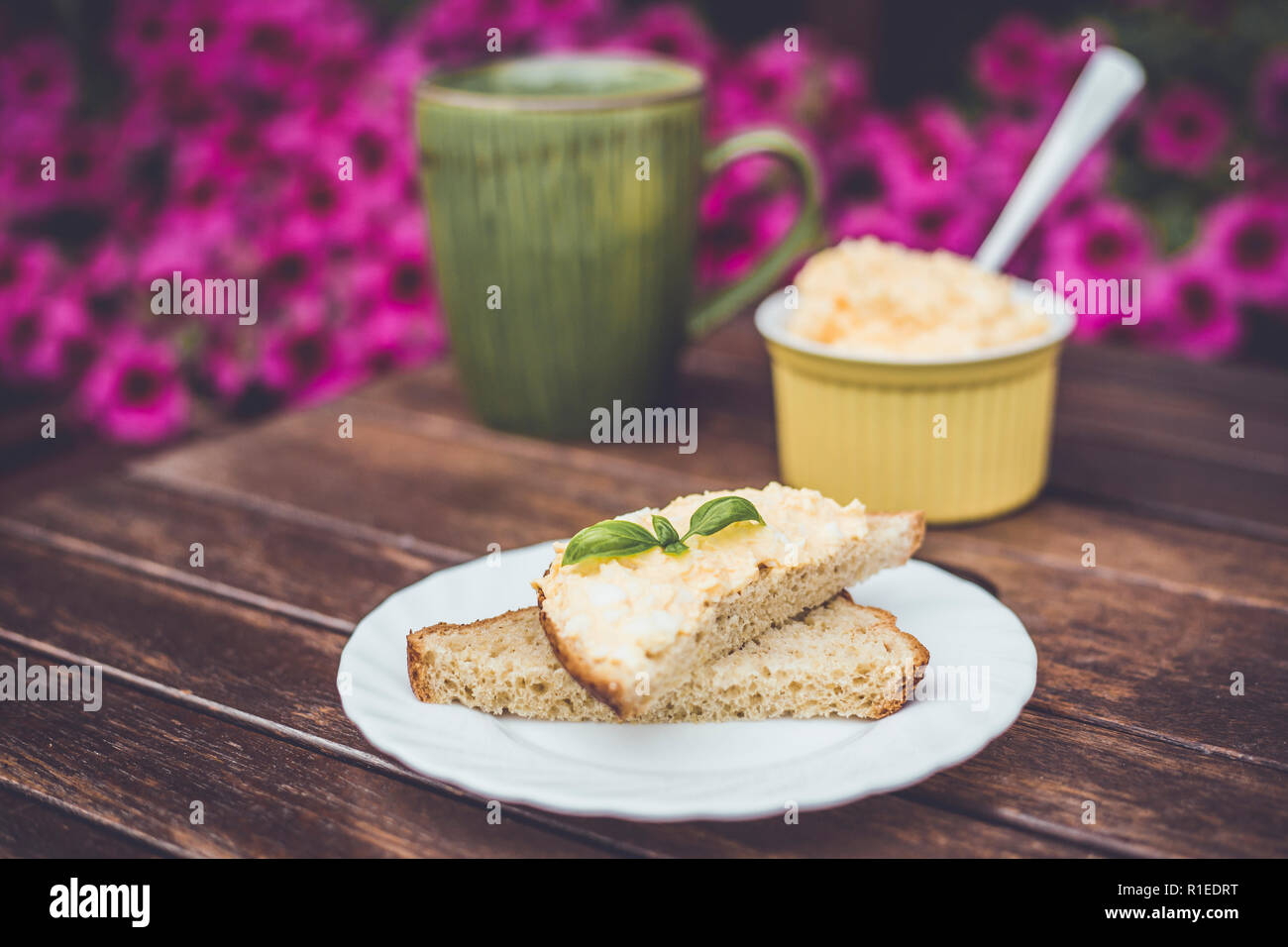 Yellow delicious egg and mayonnaise paste on whole wheat bread, breakfast snack recipe, pink flowers on the background, wooden base. - Stock Image