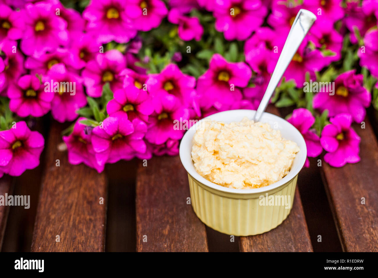 Yellow delicious egg and mayonnaise paste in yellow cup, spoon sticking out, breakfast snack recipe, pink flowers on the background, wooden base. - Stock Image