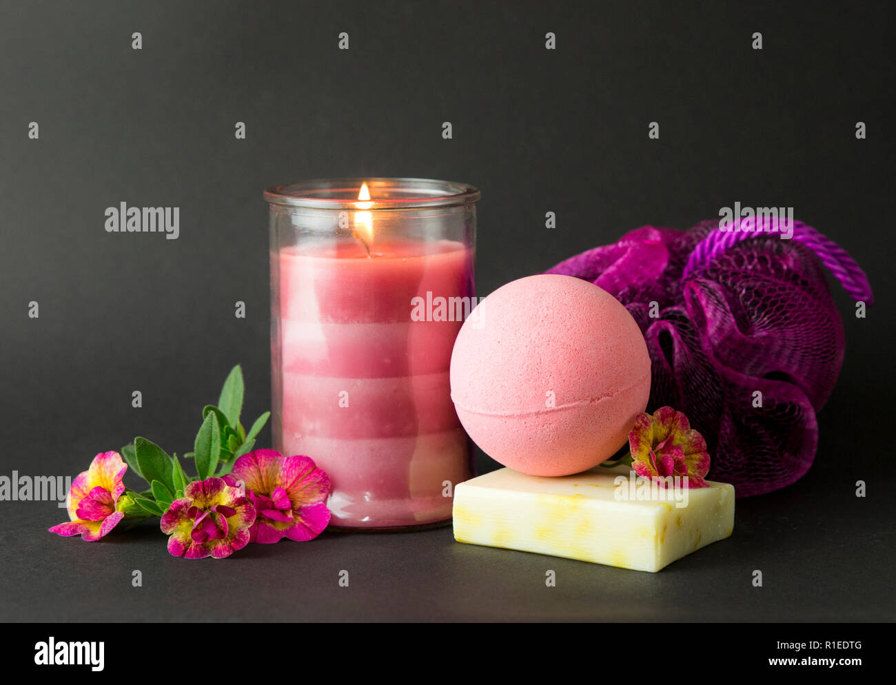 Wellness spa therapy pampering products on black background, pink candle burning, warm mood. Pink bath bomb, hand made soap, pink sponge, pink burning - Stock Image