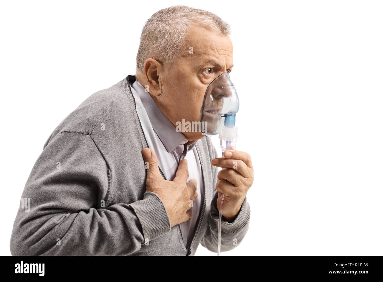 Elderly man with asthma using an inhaler and holding his chest isolated on white background - Stock Image