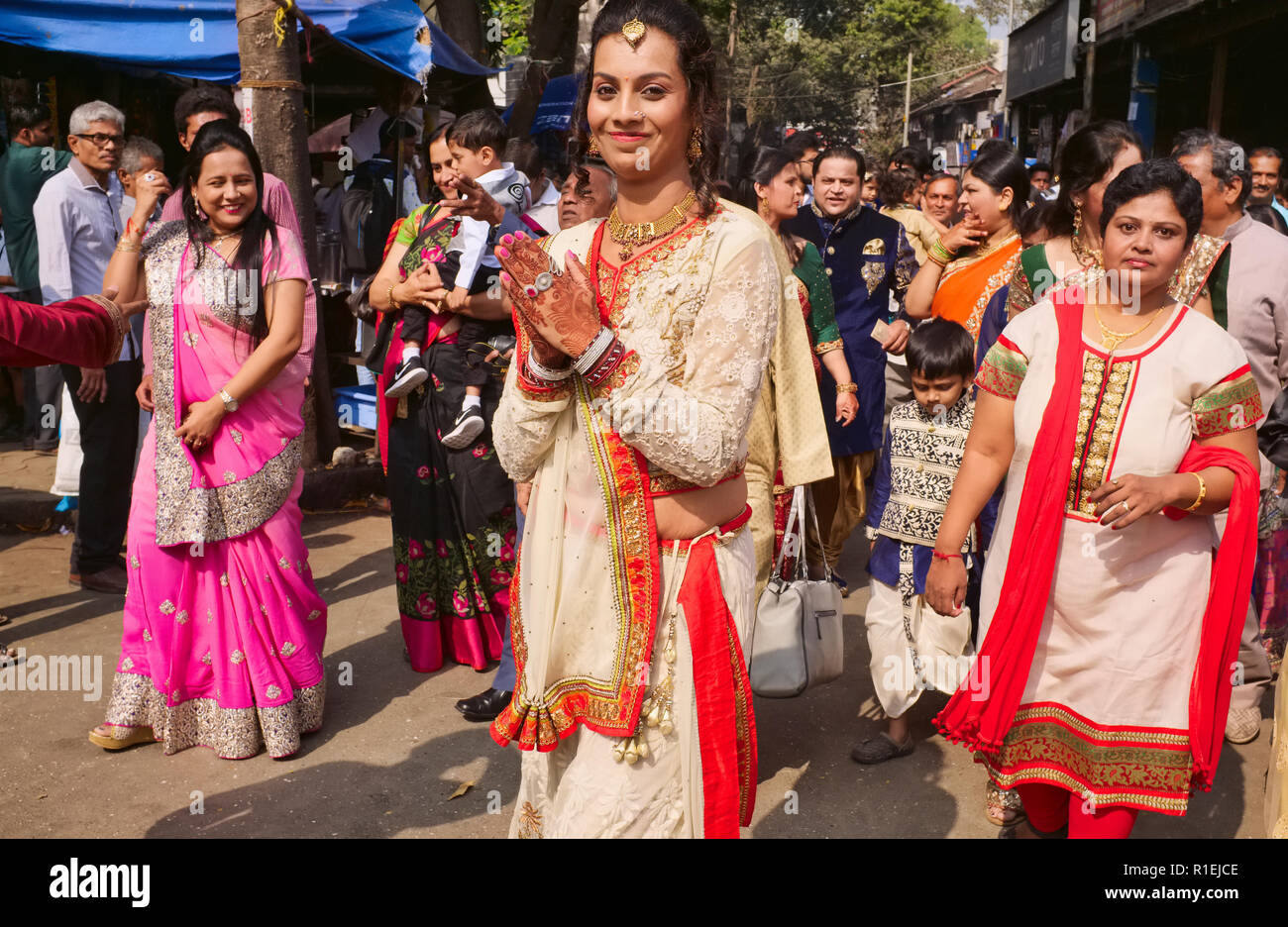 A Gujarati wedding party in Matunga, a suburb of Mumbai, India, spills out into the street, the bride up front with traditionally henna-painted hands Stock Photo