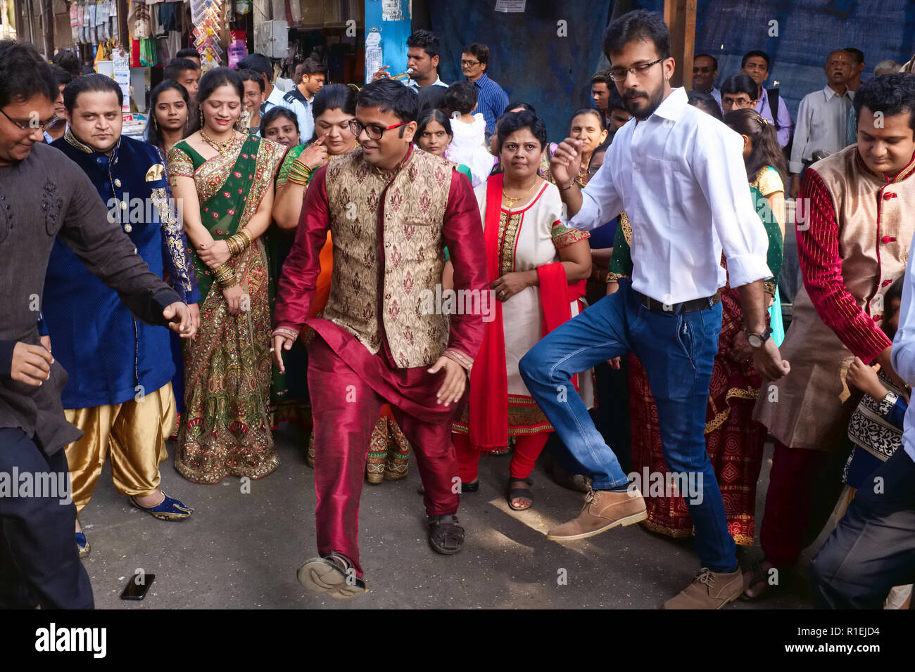 A Gujarati wedding party in Matunga, a suburb of Mumbai, India, spills out into the street, the participants dancing in the street and cheering Stock Photo
