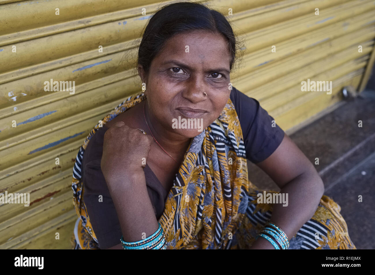 An Indian hijra, i.e. transvestite, transsexual or eunuch, taking a rest from begging near Mumbadevi Temple in Mumbai, India Stock Photo