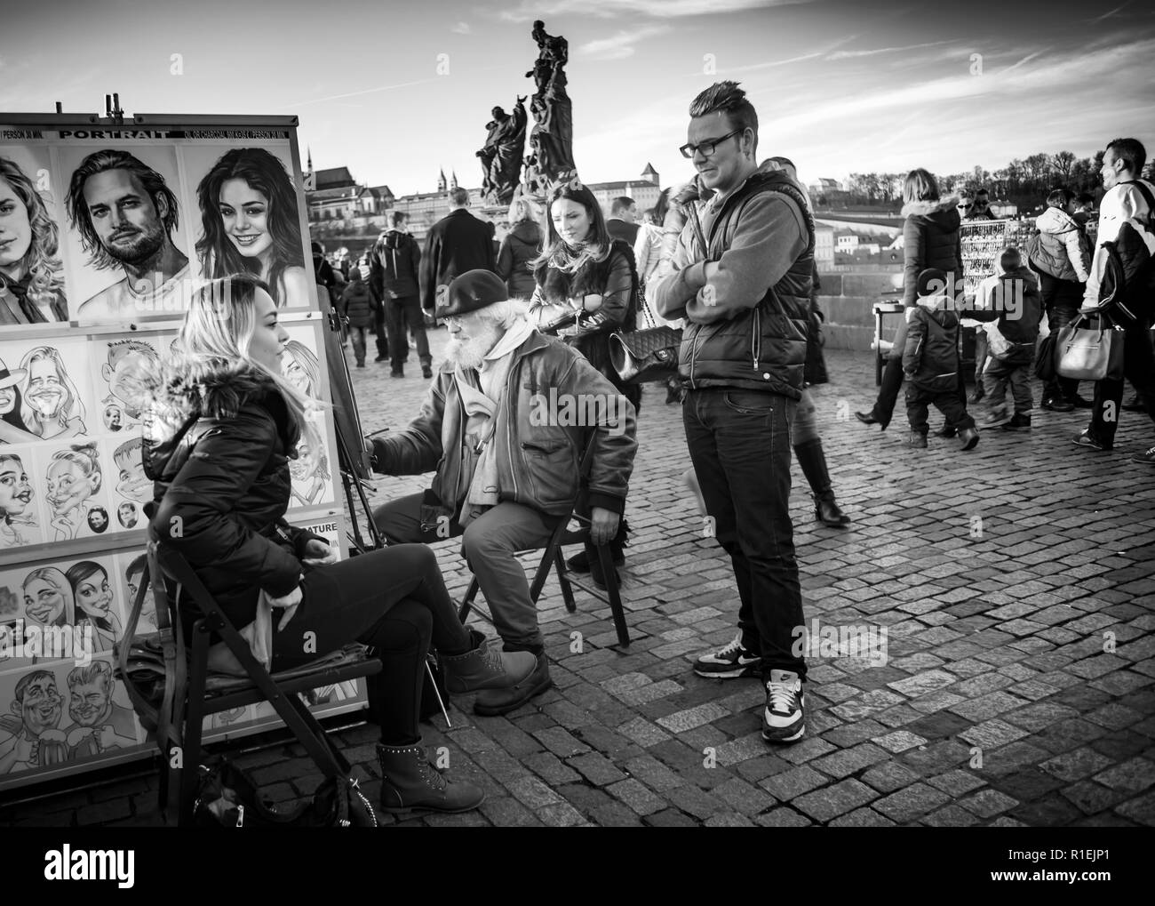 Tourists on Charles Bridge Prague, Czech Republic, with street artist getting painted in black and white Stock Photo