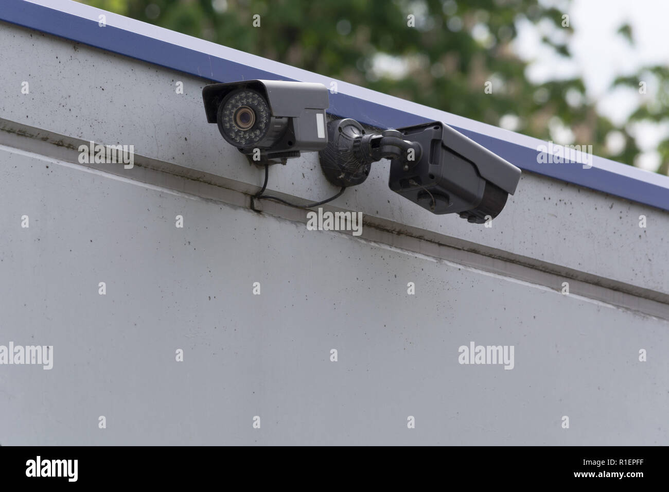 Two CCTV surveillance cameras. Concept security in the office building. - Stock Image