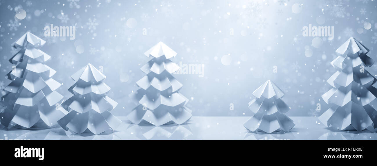 Handicrafted paper fir trees in snow - Stock Image
