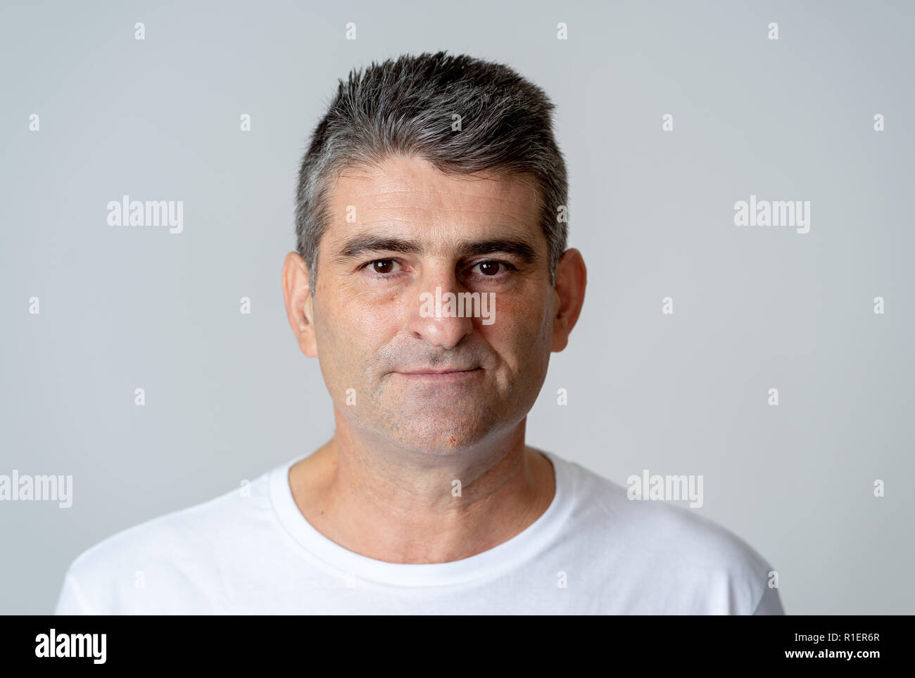 Portrait of a attractive mature man looking neutral relaxed and serious in facial expressions human emotions isolated on grey blue background. - Stock Image
