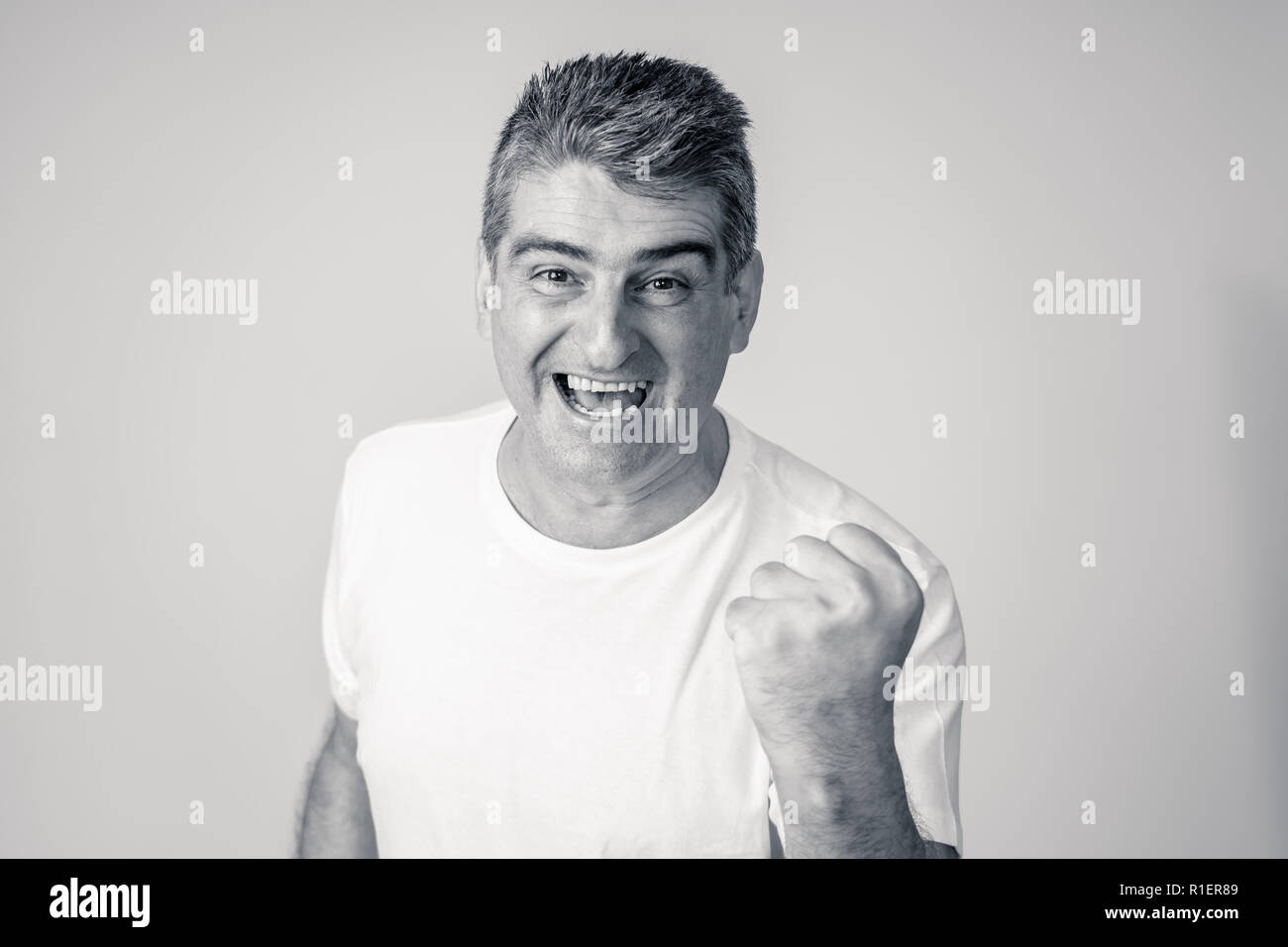 Man rejoices in achieving his goal, wining the lottery or having great success in face expression human emotions surprised and happy facial expression - Stock Image