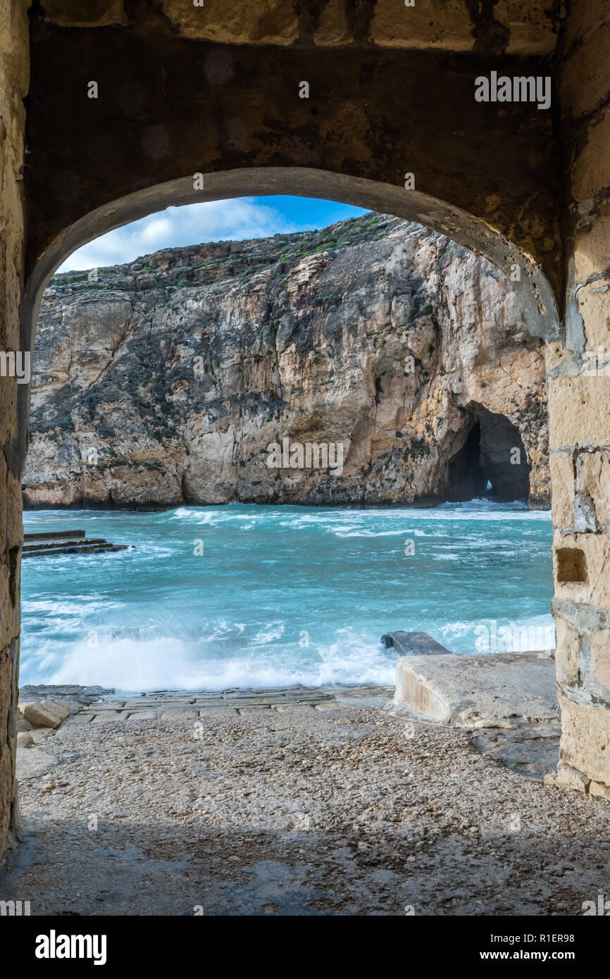 On a bright sunny winter day with rough sea in Dwejra Inland Sea. Cave that connects this little bay to the external Mediterranean clean water.  Copy  - Stock Image