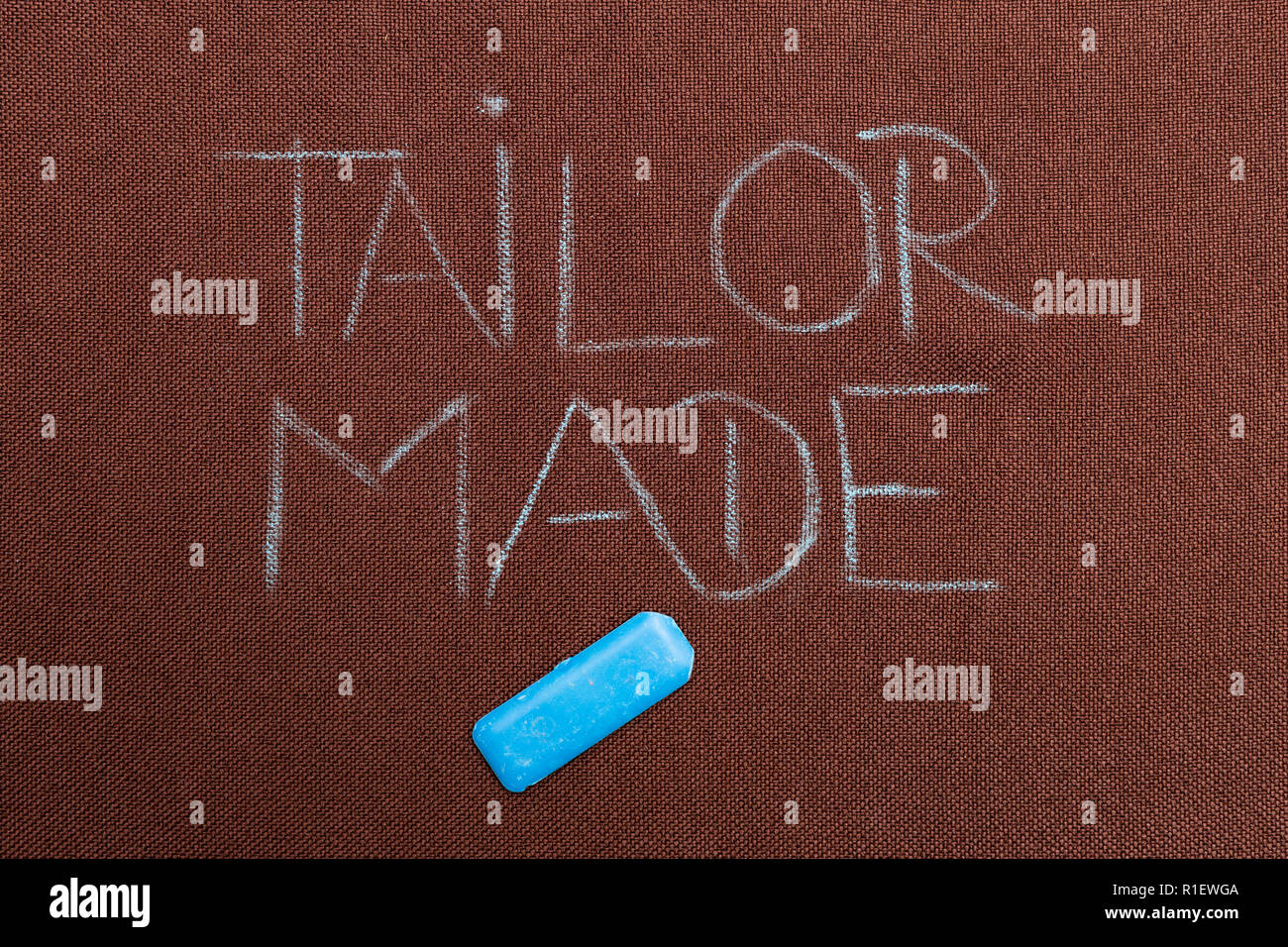 Tailor made text written on brown fabric with blue tailoring chalk underneath Stock Photo