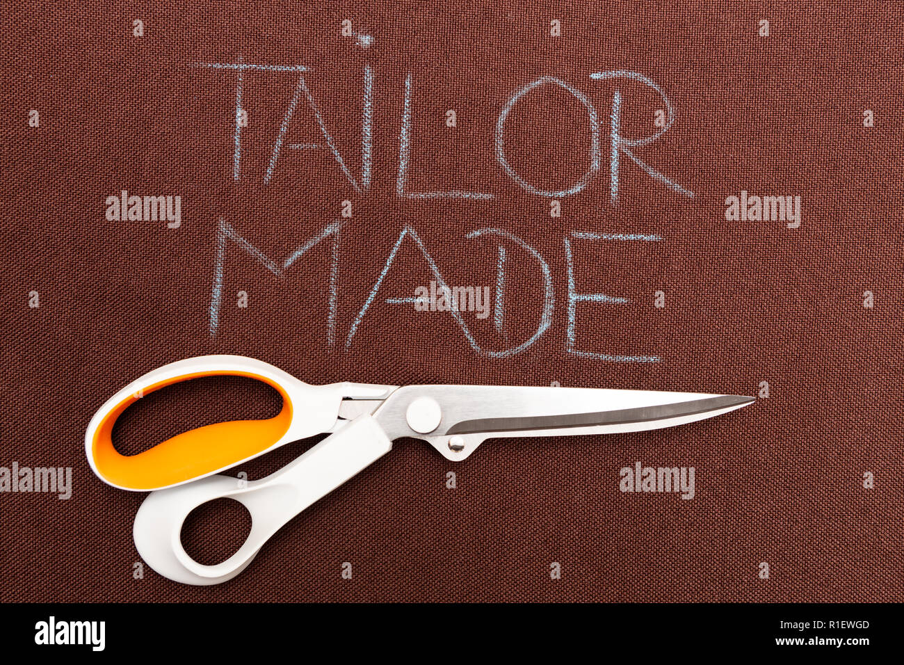 Scissors underlining tailor made text on brown fabric as background - Stock Image