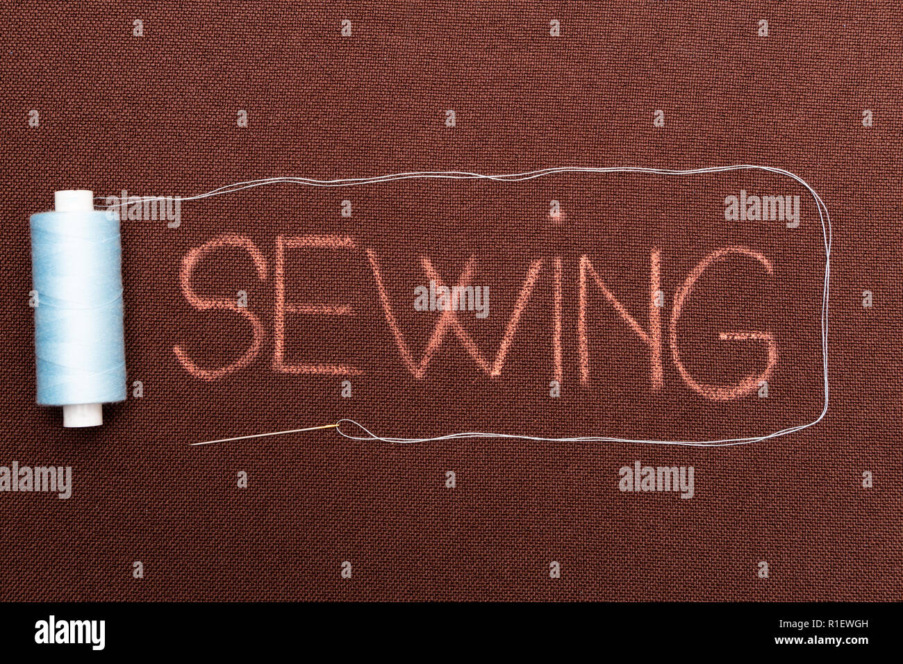 Sewing text written on brown material bordered with blue thread and needle - Stock Image
