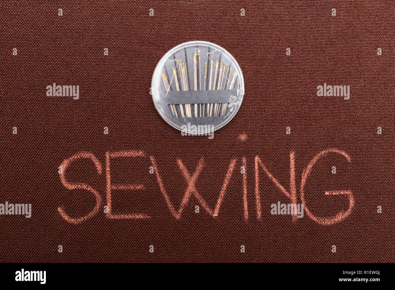 Sewing text with plastic needle holder above on brown fabric background - Stock Image