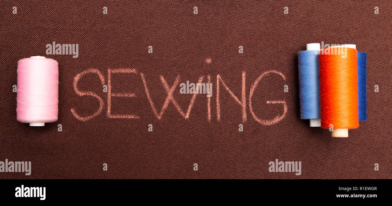Sewing text in red flanked by colourful spools of thread written on brown fabric - Stock Image
