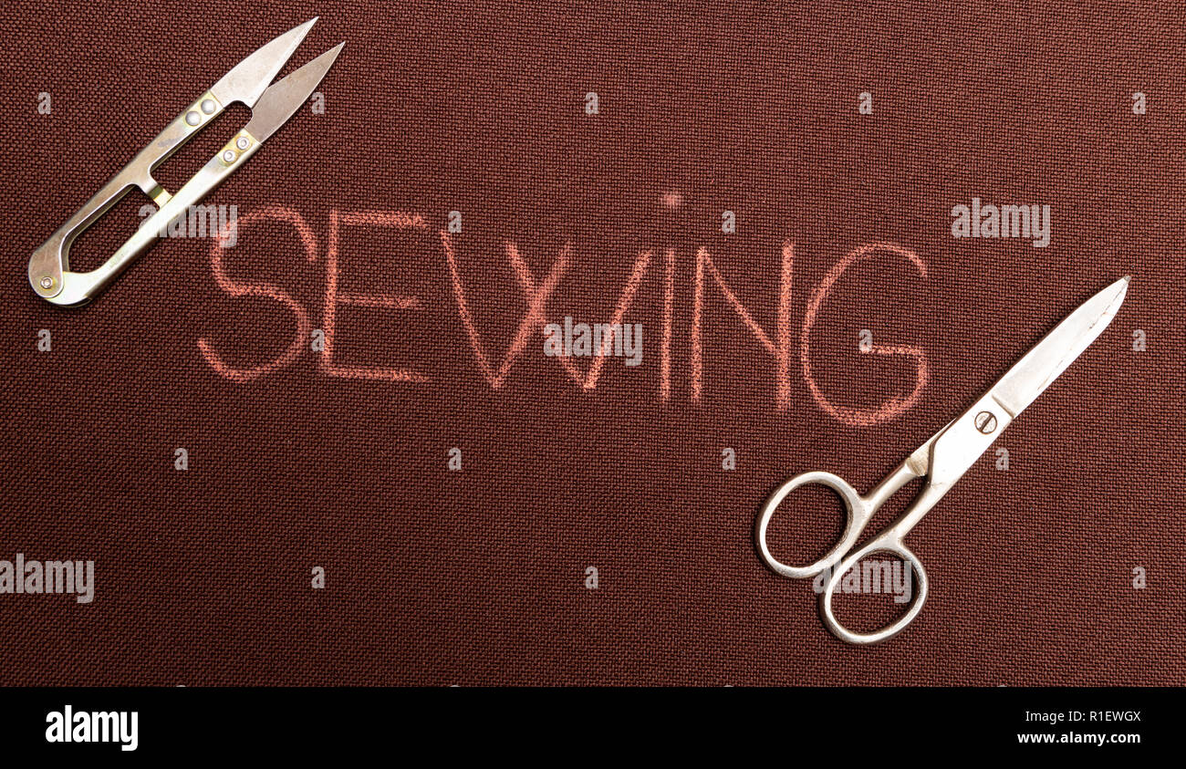 Sewing written on brown fabric with scissors in two corners of text - Stock Image