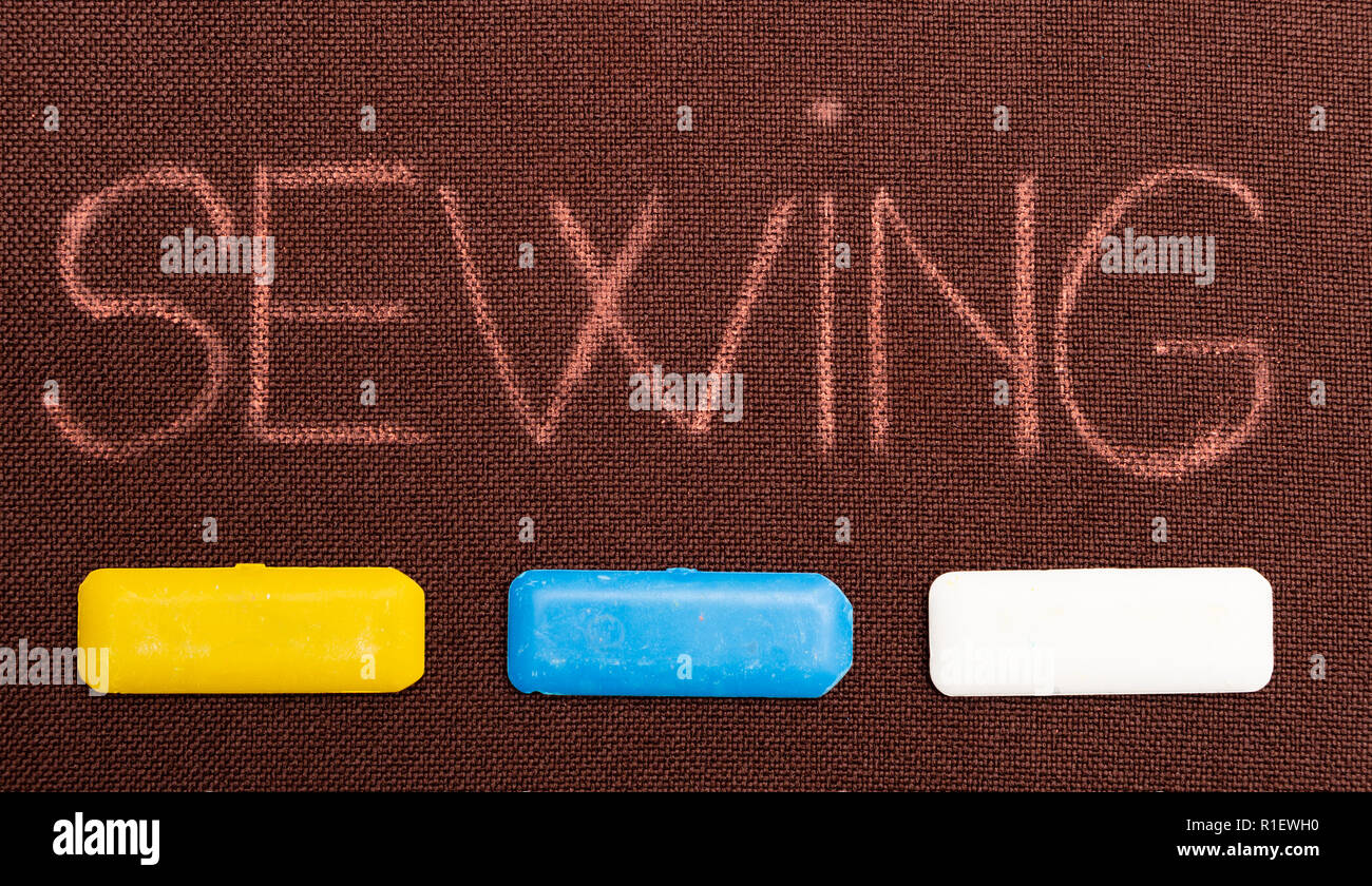 Sewing text underlined by yellow, blue and white tailoring chalks on brown fabric as background - Stock Image