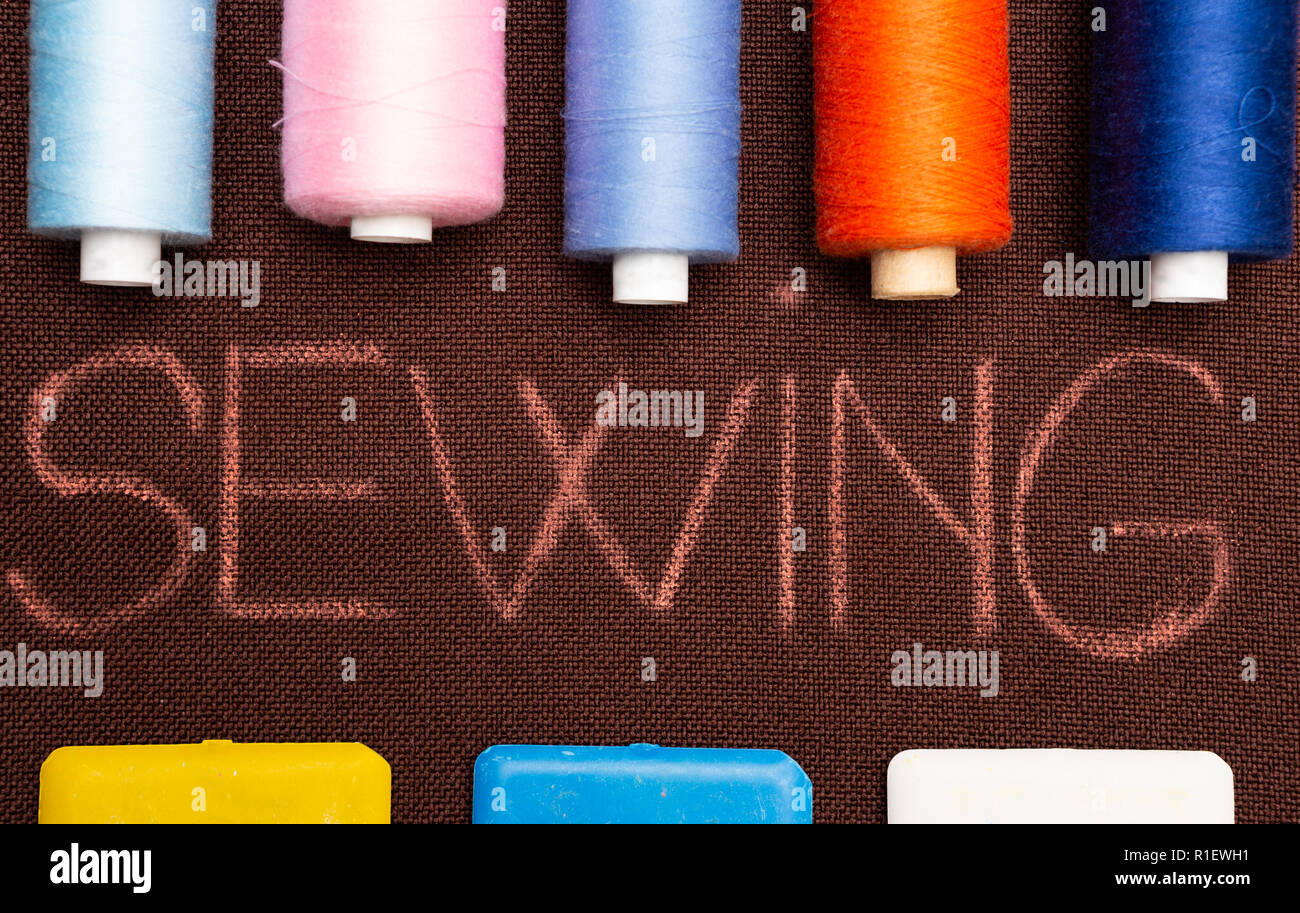 Sewing text on brown fabric framed by tailoring supplies such as colourful chalk and thread spools Stock Photo