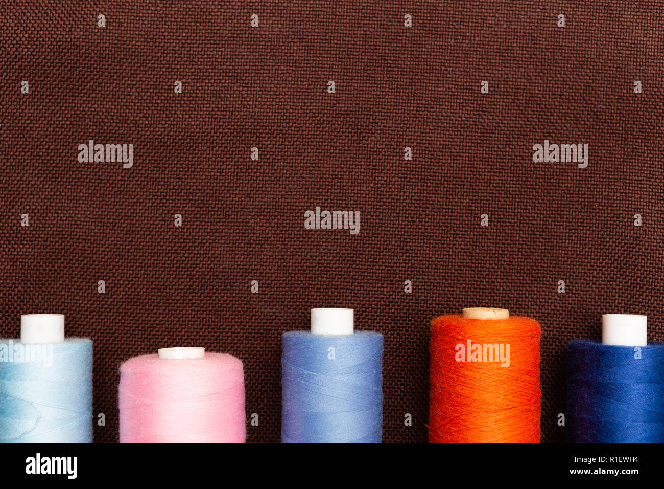 Thread spools on brown fabric background with blank copyspace for advertising Stock Photo