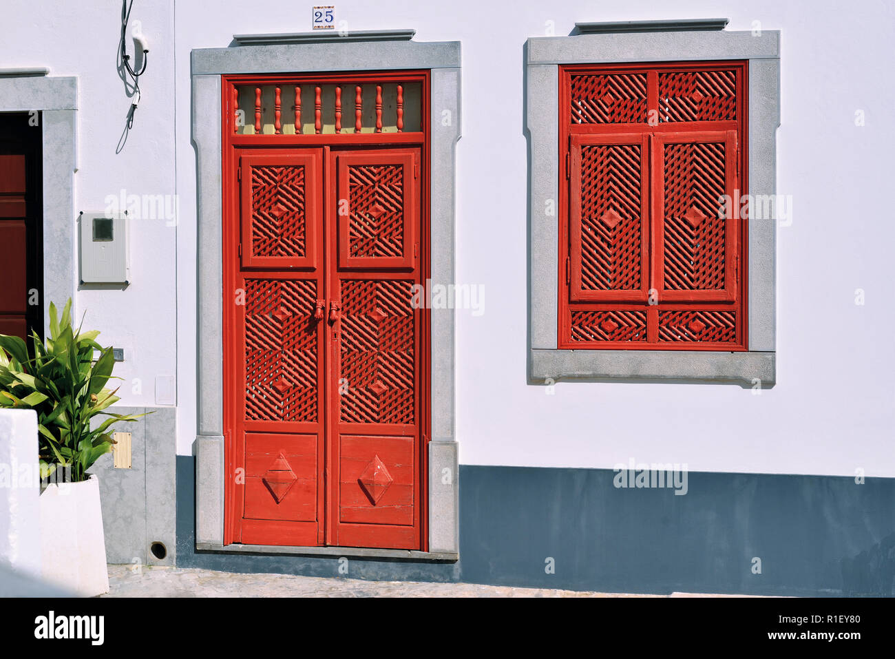 Red door and window in traditional arabian style with various divisions in recently restored small house - Stock Image