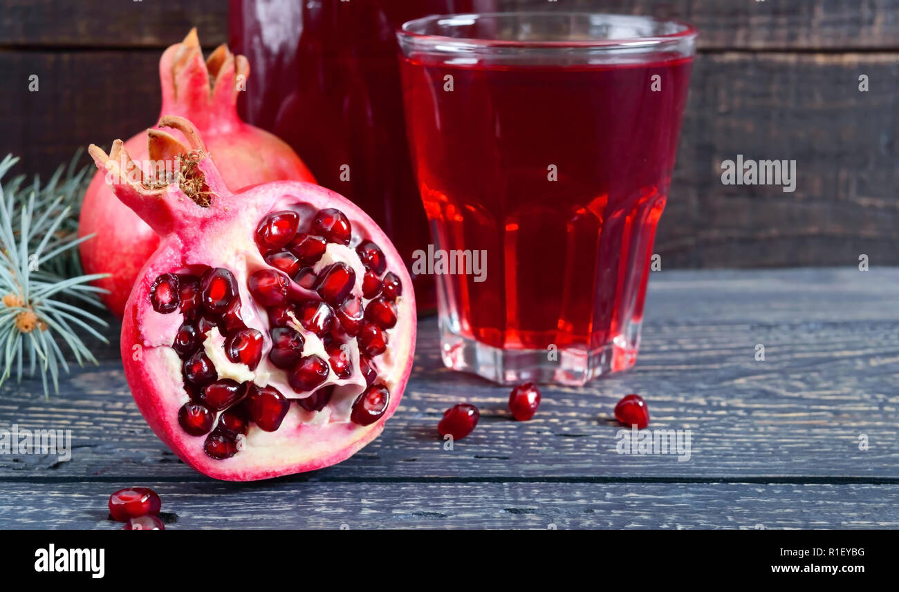 A glass of fresh pomegranate juice with ripe pomegranate fruits on wooden table. Vitamins and minerals. Healthy drink concept. Close up - Stock Image
